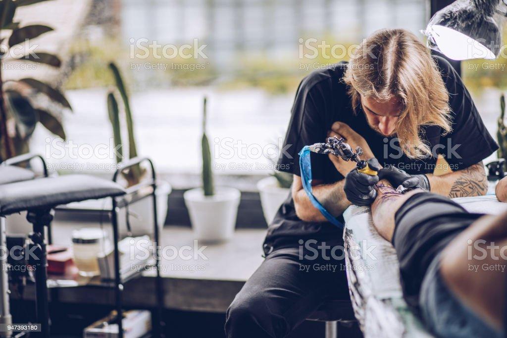 Guy getting a new leg tattoo stock photo