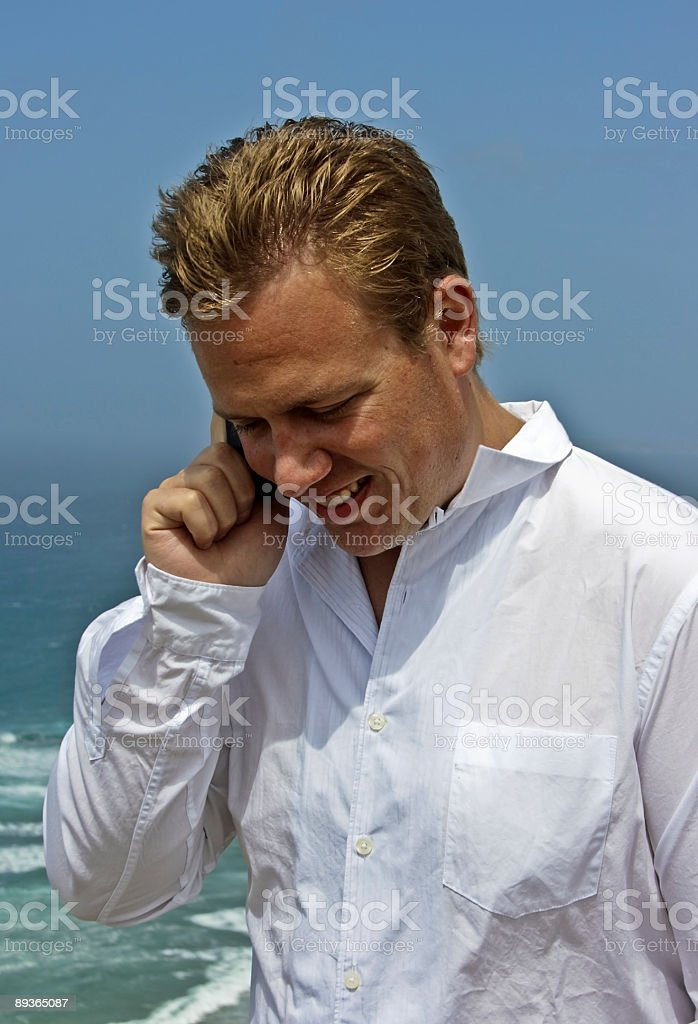 Guy having a phone call on holiday at the beach royalty-free stock photo