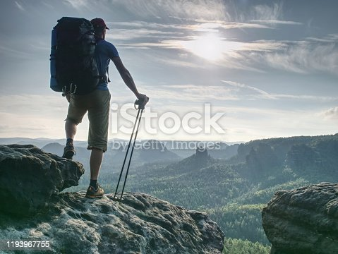Guy hold sticks in one hand. Hiker stop for watching landscape from sharp sandstone summit.