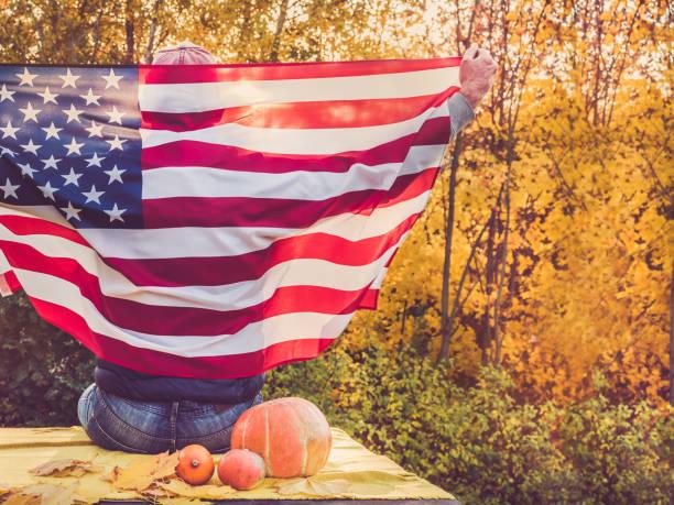 guy holding a us flag. national holiday - veterans day стоковые фото и изображения
