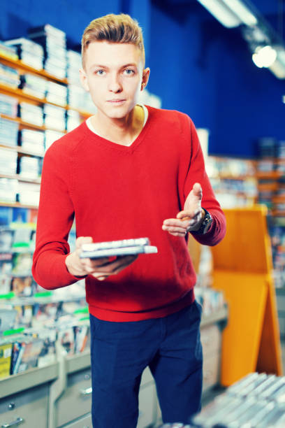 guy holding cd im shop - cd ständer stock-fotos und bilder