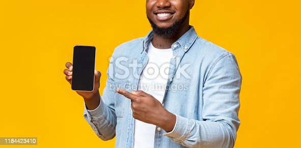 istock Guy holding cellphone with black screen and pointing on it 1184423410