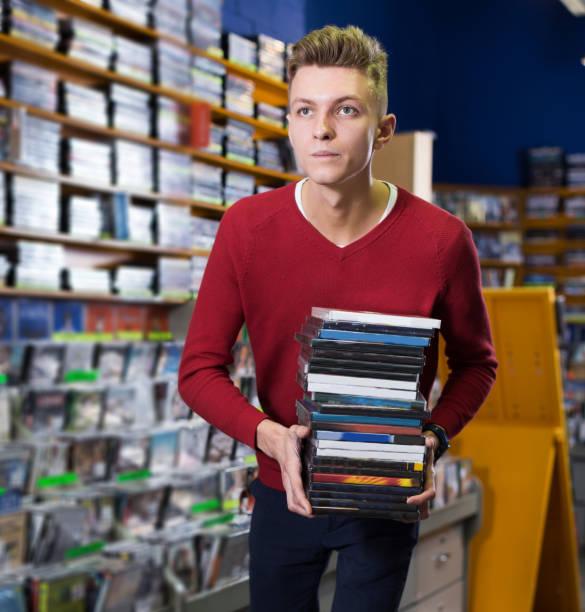 mann hält stapel von kisten mit dvds - cd ständer stock-fotos und bilder