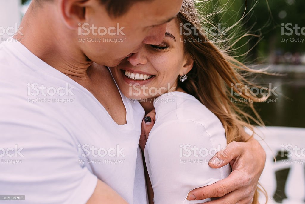 guy hugging his girlfriend stock photo
