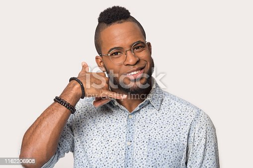 Head shot portrait isolated on grey or white background millennial mixed race guy in glasses look at camera imitating telephone gestures makes with hand call me, mobile wireless communication concept