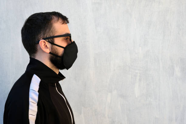 A guy in a black mask and glasses stands sideways to the camera against a gray wall. A guy in a black mask and glasses stands sideways to the camera against a gray wall. The theme of the pandemic and the crown of the virus, the need to wear masks to protect against infections. Mockup armenian ethnicity stock pictures, royalty-free photos & images