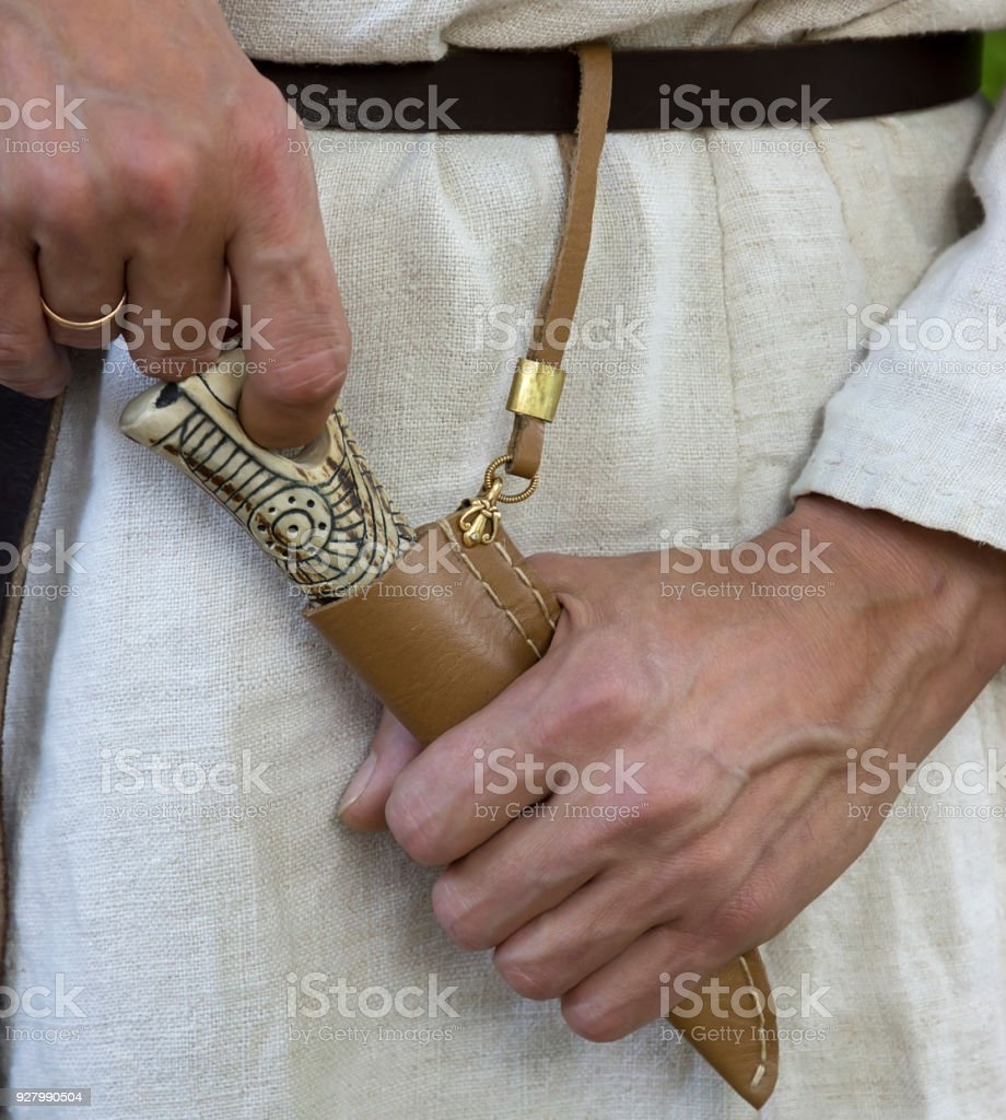 A guy in a national ethnic linen suit pulls a knife out of the foot with a hand-worked hilt. Festival of Medieval Culture. stock photo