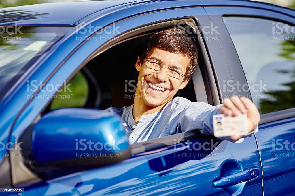 Guy in car with driving license stock photo