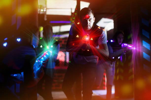 Cara em feixes coloridos durante jogo de laser tag - foto de acervo