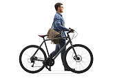 istock Guy in denim clothes walking and pushing a bicycle 1187248782