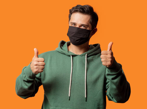 guy in face mask and green hoodie stock photo