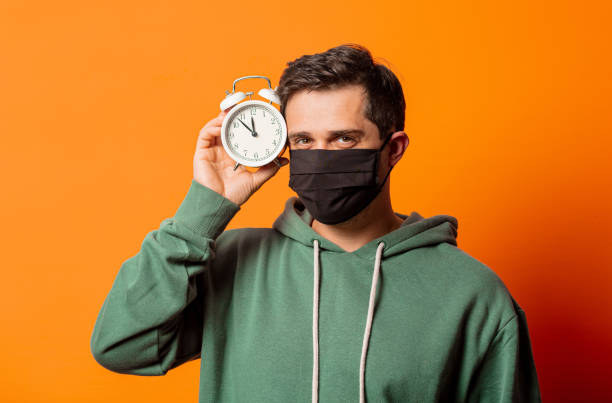 guy in face mask and green hoodie with alarm clock stock photo