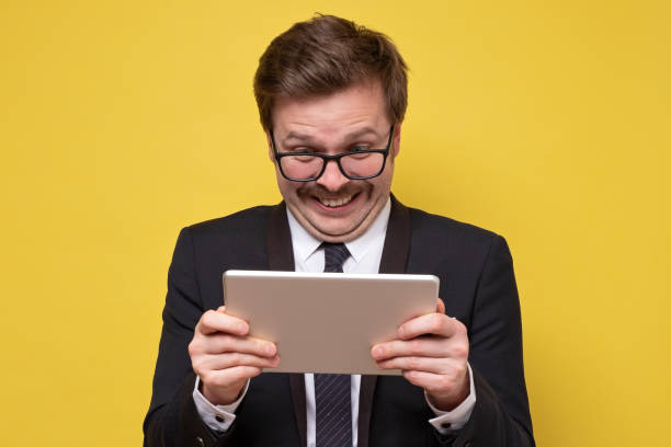 Guy in glasses holding using digital tablet looking shocked about social media news stock photo