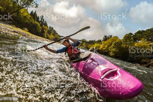 Photo of Guy in kayak sails mountain river.