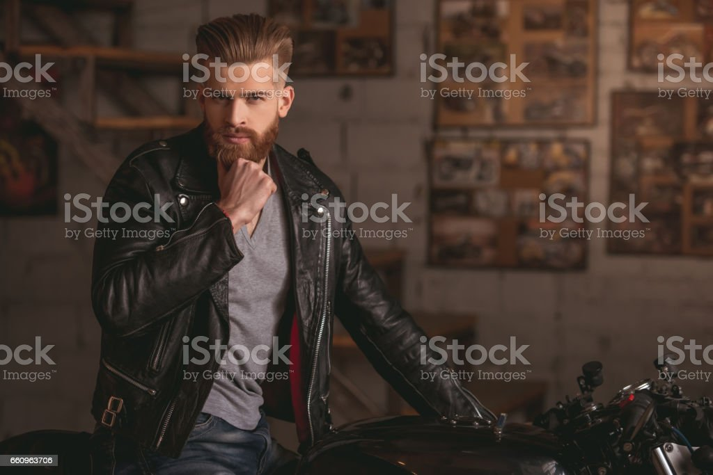 Guy in motorbike repair shop stock photo