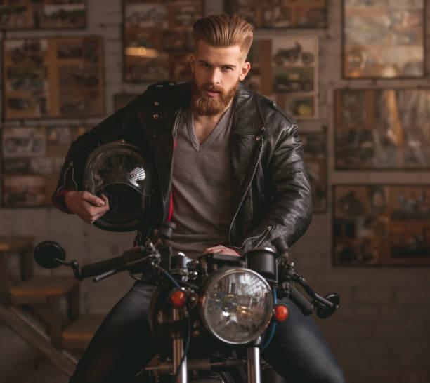 guy in motorbike repair shop - motorrad männer stock-fotos und bilder