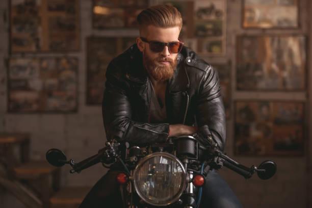guy in motorbike repair shop - biker stock photos and pictures