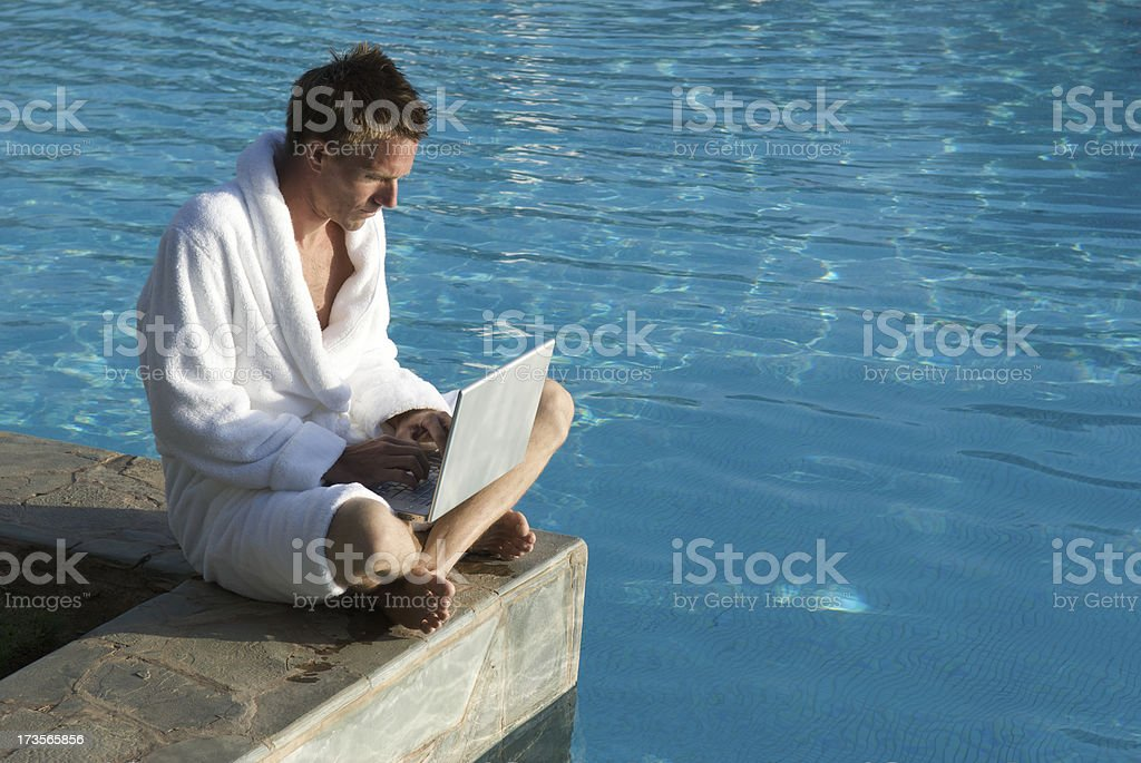 Guy in Robe Poolside with Laptop royalty-free stock photo