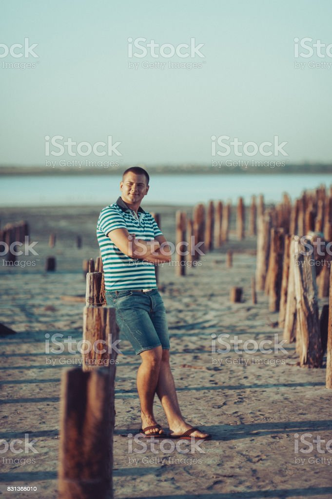 Guy in shorts and a T-shirt is standing near the posts on the estuary stock photo