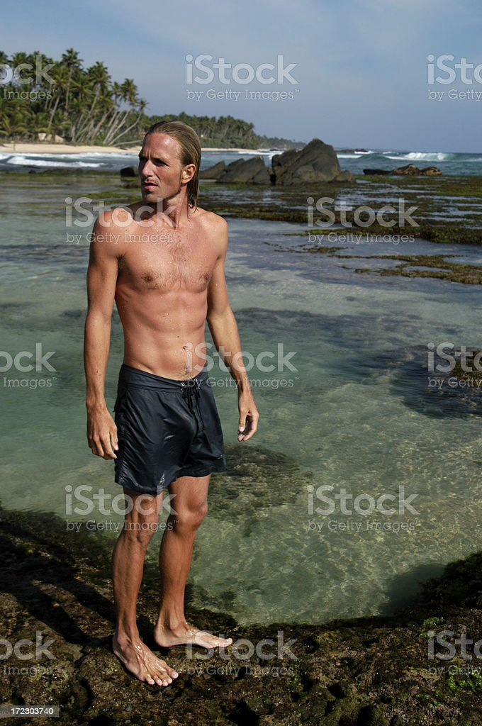 Guy in Shorts Stands Next to Tropical Lagoon royalty-free stock photo