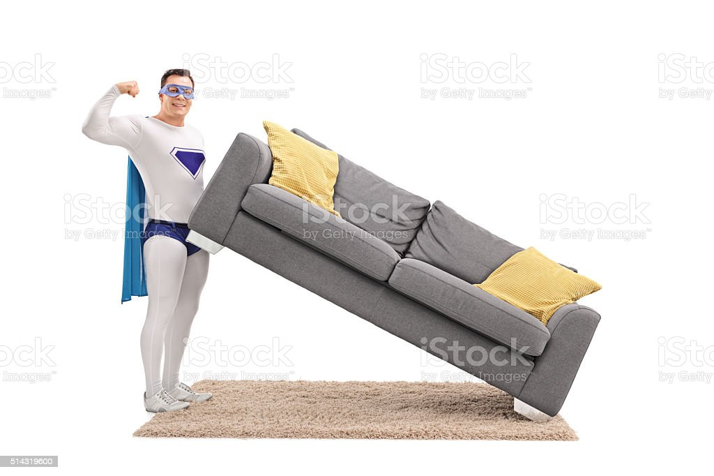 Guy in superhero costume lifting a sofa with one hand stock photo
