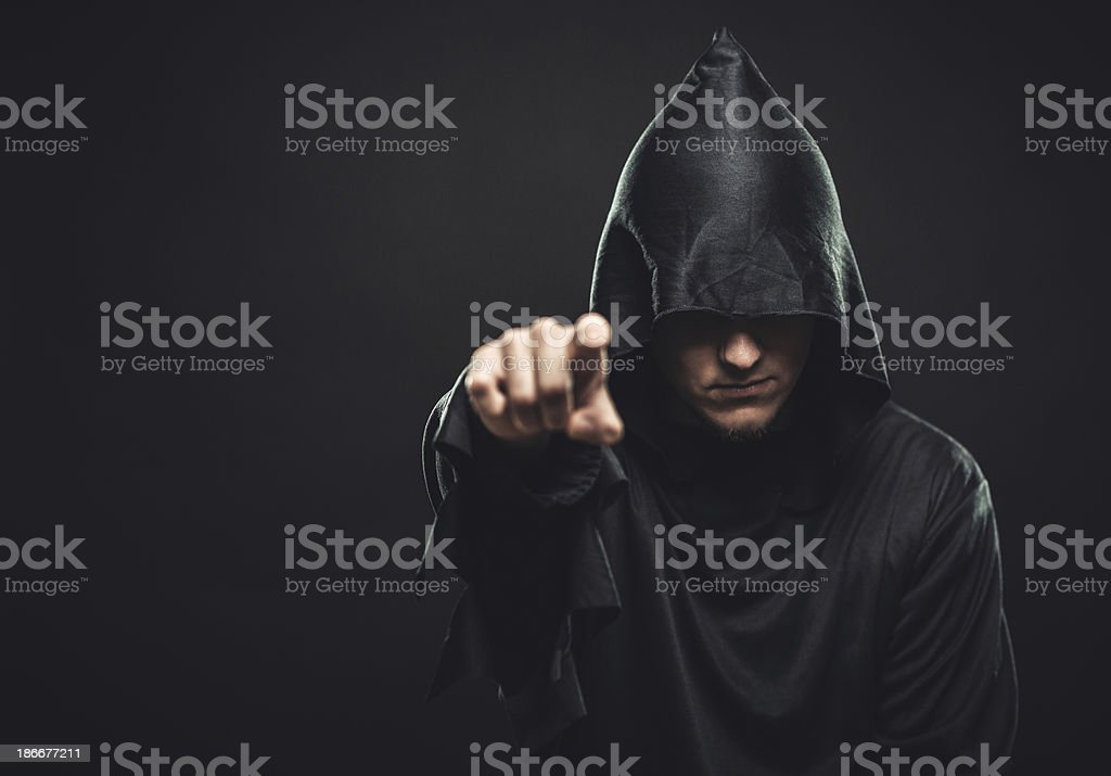 guy in the black robe indicates you stock photo