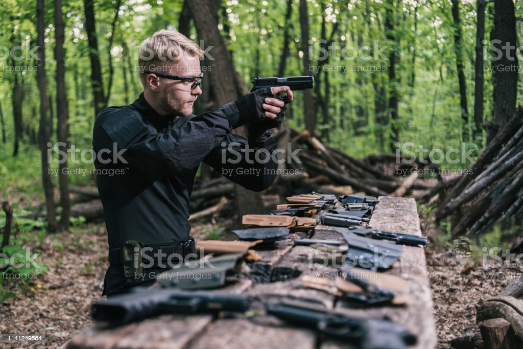 the guy in the woods is cleaning his weapon