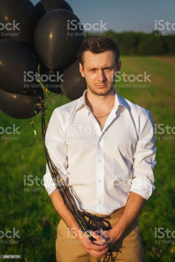 guy in white shirt with black balloons standing in a stock photo