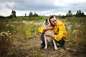 Side view of young man sitting and hugging with beige Labrador retriever in blooming meadow with cloudy sky on background