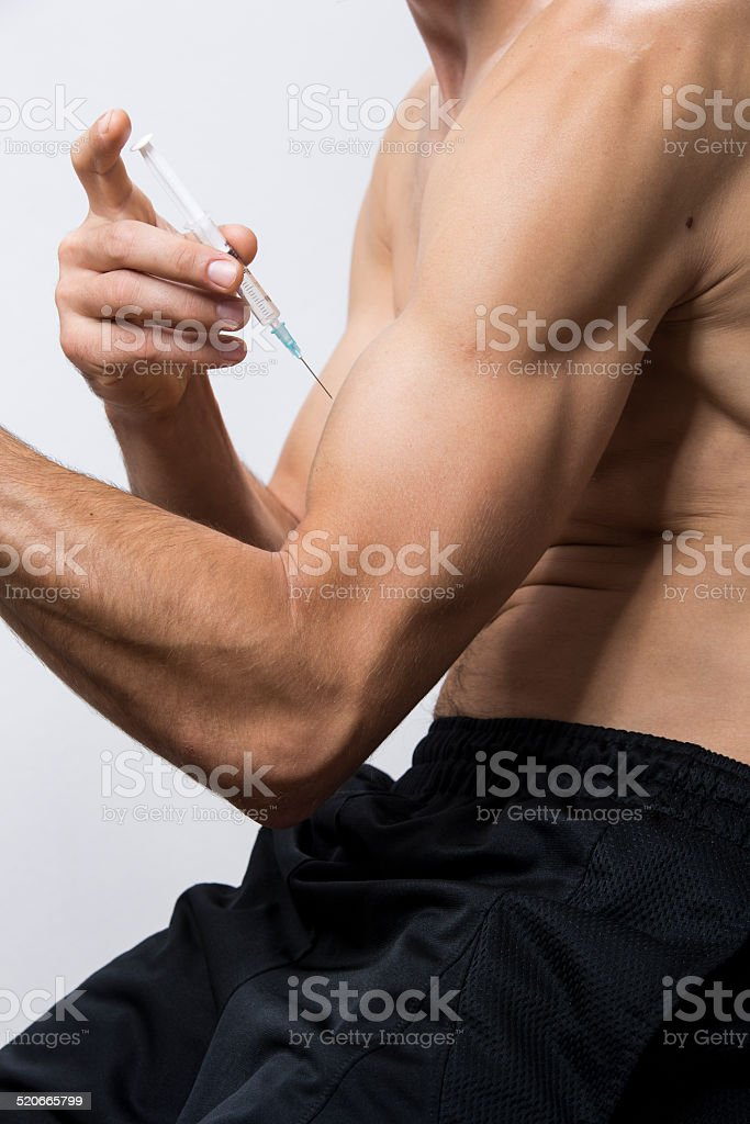 Guy injecting steroids into biceps stock photo
