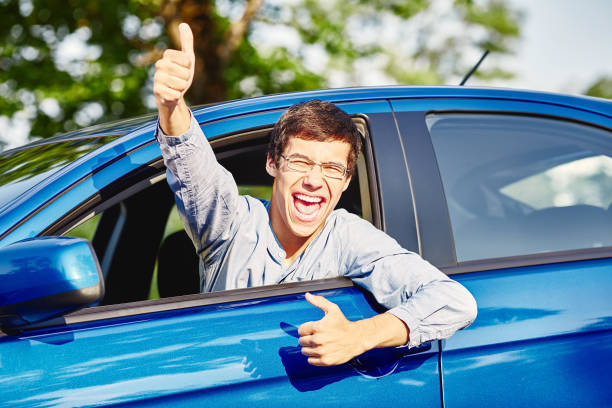 Guy inside car showing thumbs up Close up of young hispanic man wearing glasses showing thumb up hand gesture and happy screaming through car window - driving school and new drivers concept passed driving test stock pictures, royalty-free photos & images