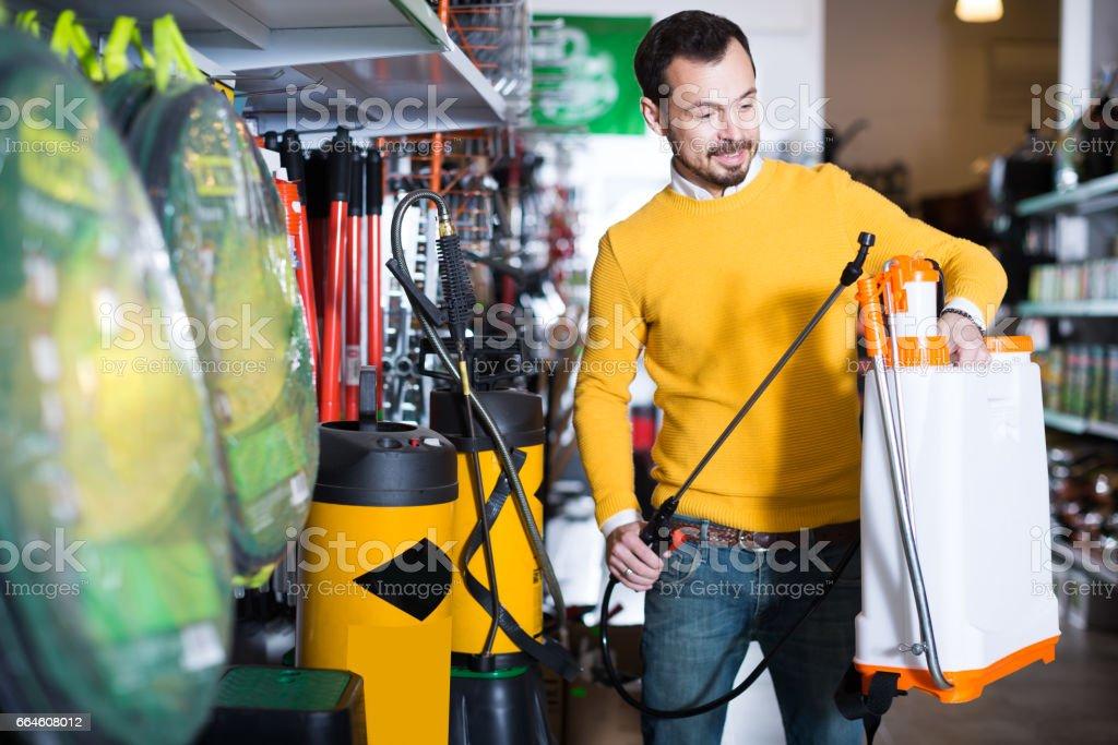 Guy is considering an assortment of garden sprayers stock photo