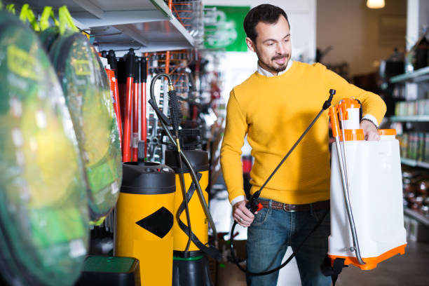 Guy is considering an assortment of garden sprayers stock photo