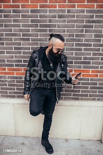 Bearded biker in leather jacket standing on the street and text messaging.