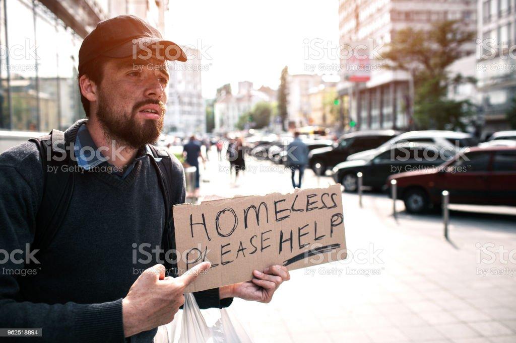 Guy is standing on the street and pointing on piece of cardboard which says homeless please help. Guy is begging for money and help. He is in despair - Royalty-free Adult Stock Photo