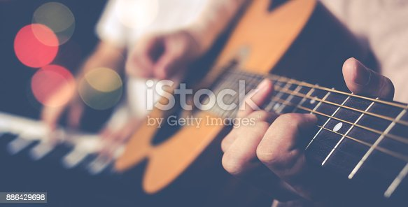 guy jamming acoustic guitar with piano player background