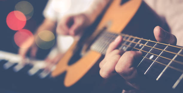 guy jamming acoustic guitar with piano player background stock photo