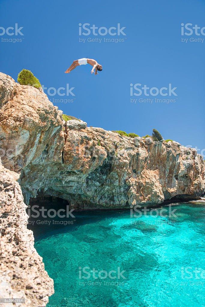 Chico Saltar de un acantilado en el océano, Mallorca, España - foto de stock