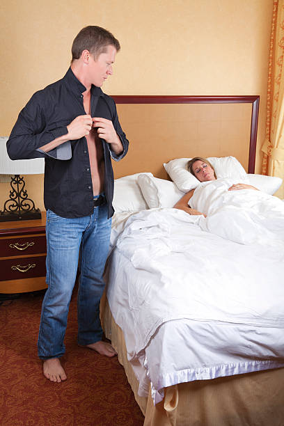 Guy leaving in the morning while girl sleeps  real couples making love stock pictures, royalty-free photos & images