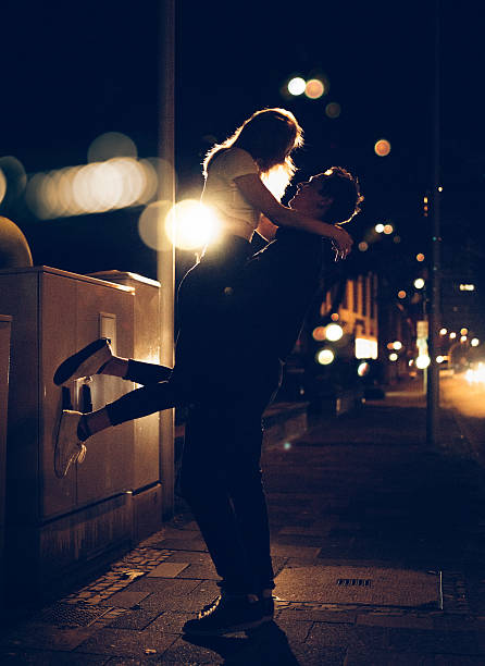 Guy lifting up his girlfriend on late night city street stock photo