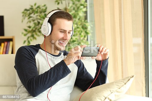 istock Guy listening and watching media in a smartphone 657006410