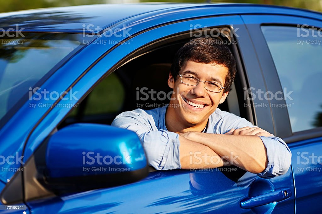 Guy looking out through open car window stock photo