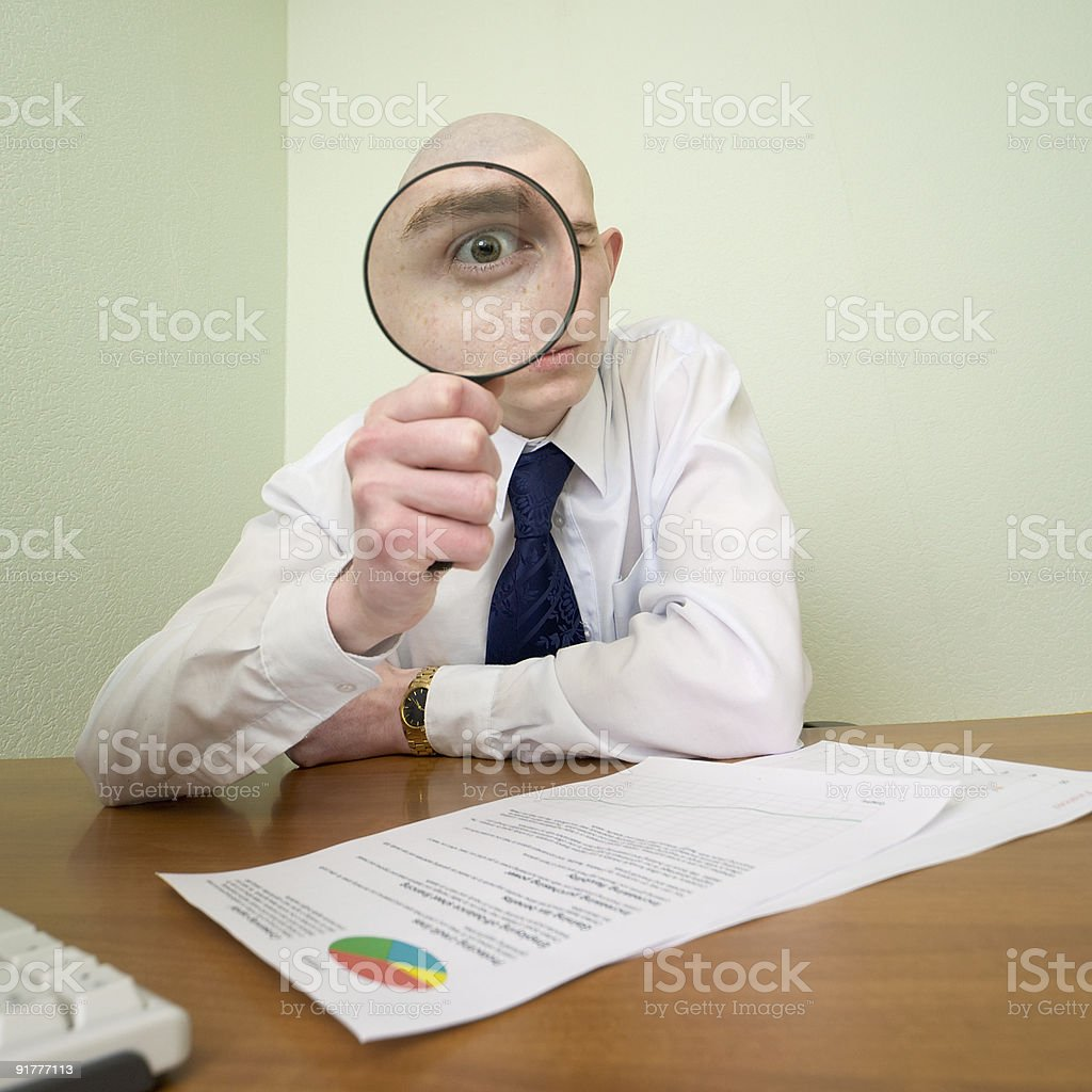 Guy looks through the magnifier royalty-free stock photo