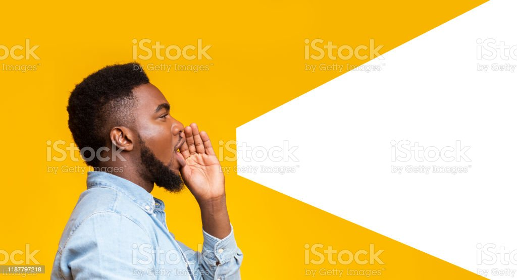 Guy making loud announcement at copy space on yellow background African american man making loud announcement at copy space, holding hand near his open mouth over yellow background, side view Adult Stock Photo