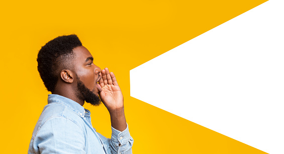 Guy Making Loud Announcement At Copy Space On Yellow Background Stock Photo - Download Image Now