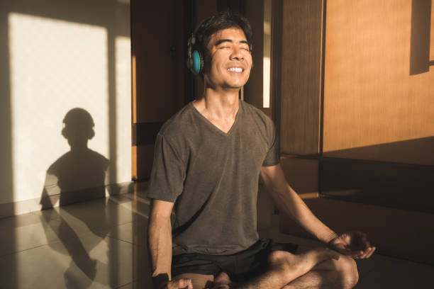 Guy meditating yoga lotus pose with eyes closed sitting on the floor at home stock photo