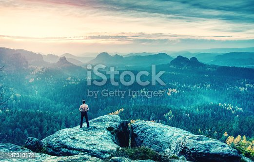 Guy on a cliff above fairy misty valley. Cracked Rock, the most famous tourist attraction.