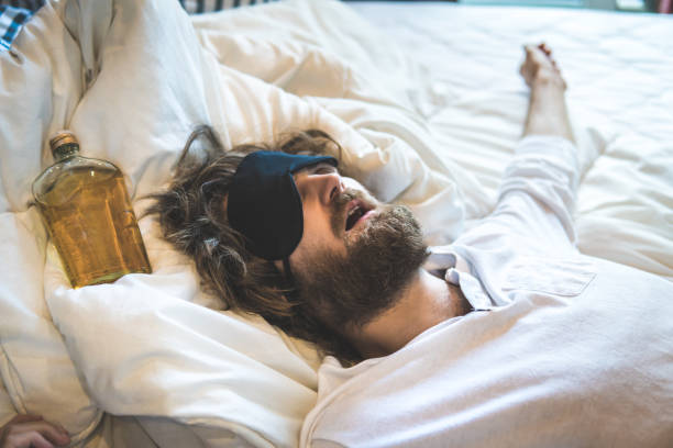 Guy passed out in bed after drinking alcohol excessively. The day after hangover and intoxication. Guy passed out in bed after drinking alcohol excessively. The day after hangover and intoxication. aftereffect stock pictures, royalty-free photos & images