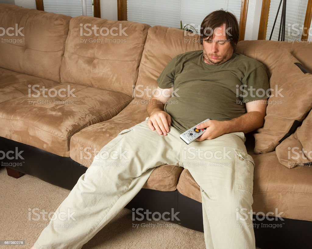 Guy passed out on the couch stock photo