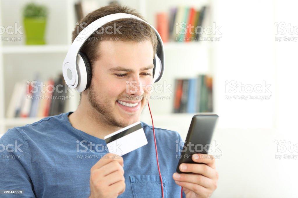 Guy payant de musique en streaming avec carte de crédit - Photo
